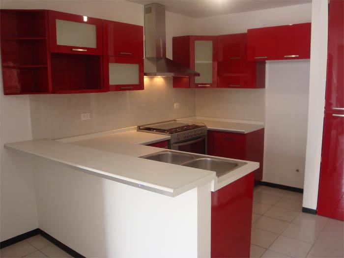 Cocina alto brillo rojo con cubierta de Corian blanco, puertas lisas